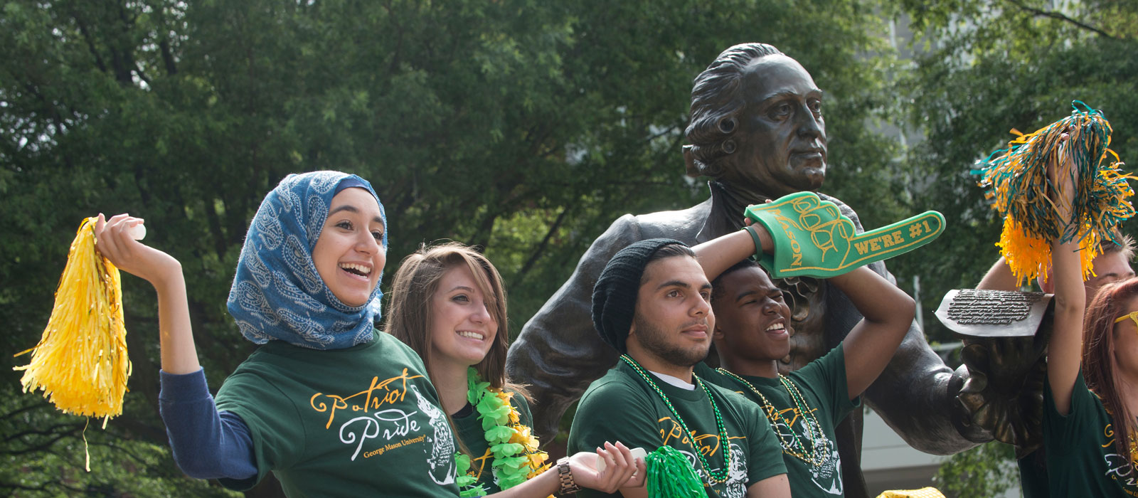 New fresman students celebrate at the George Mason statue on the Fairfax Campus